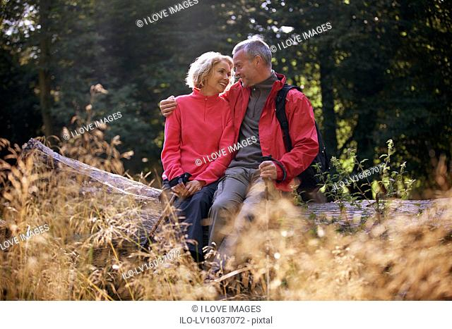 A mature couple sitting on a tree trunk embracing