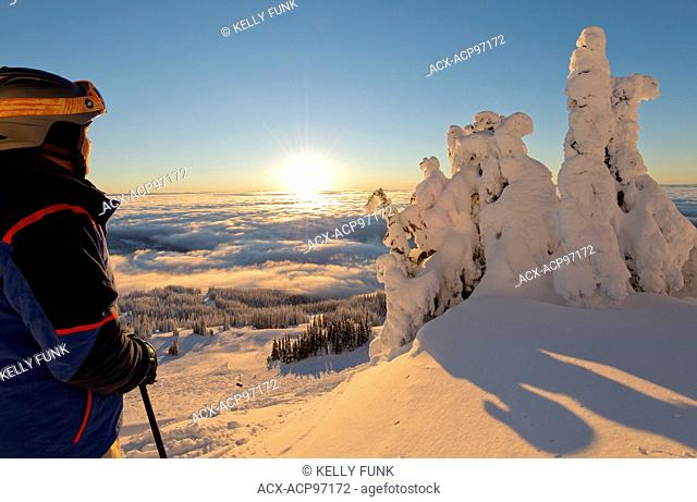 A skier rests among the snow ghosts while surveying the beautiful landscape at sunrise at the top of Sun Peaks Resort, Thompson Okangan region, British Columbia