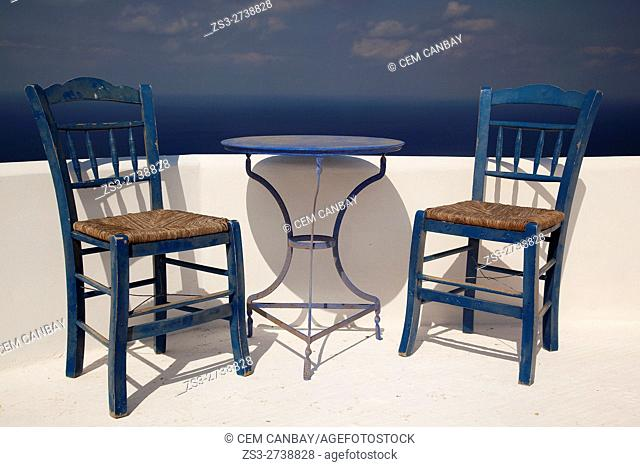 Traditional Greek chairs and table looking out to the sea in the village of Kastro or Castle, Sikinos, Cyclades Islands, Greek Islands, Greece, Europe