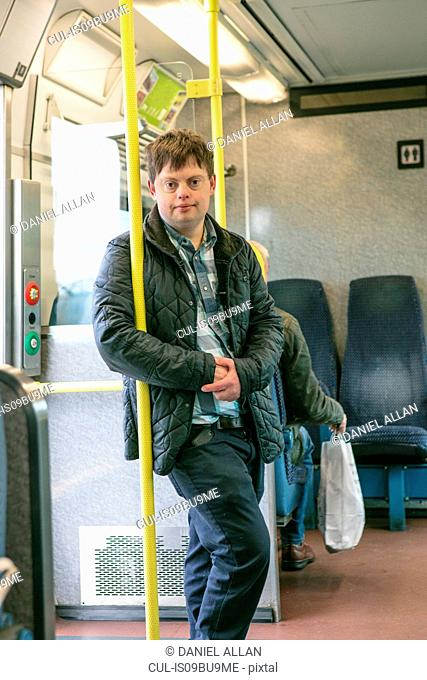Man with down syndrome holding onto hand pole in train