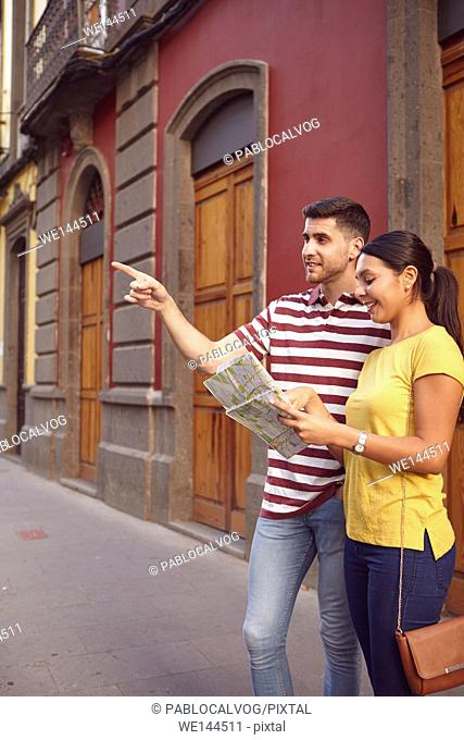 Cute young couple studying a map and pointing to their front while smiling happily and dressed casually in t-shirts with old buildings behind them