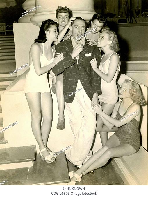 Actor Mischa Auer with a lot of women