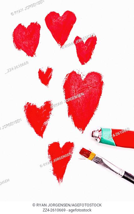 The art of love symbolised in a oil painting of hearts with brush and paint. Relationship conceptual artwork