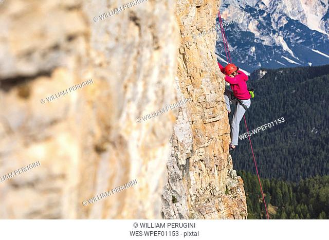 Italy, Cortina d'Ampezzo, woman climbing in the Dolomites mountains