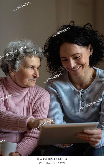 Mother and daughter using digital tablet in living room
