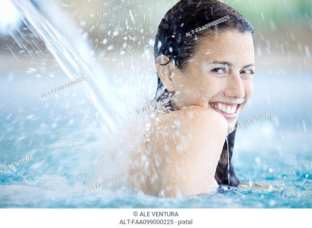 Woman relaxing under fountain in swimming pool