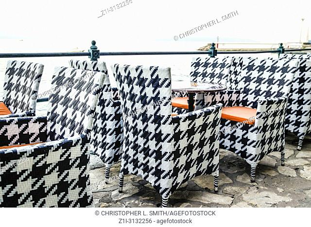 Empty waterfront cafe chairs and tables in Opatija, Croatia