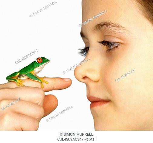 Girl with a red-eyed tree frog on her finger