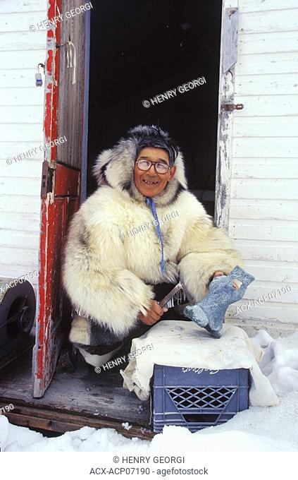 Inuit elder works on soapstone carving in traditional clothing, Kimmirut, Baffin Island, Nunavut, Canada