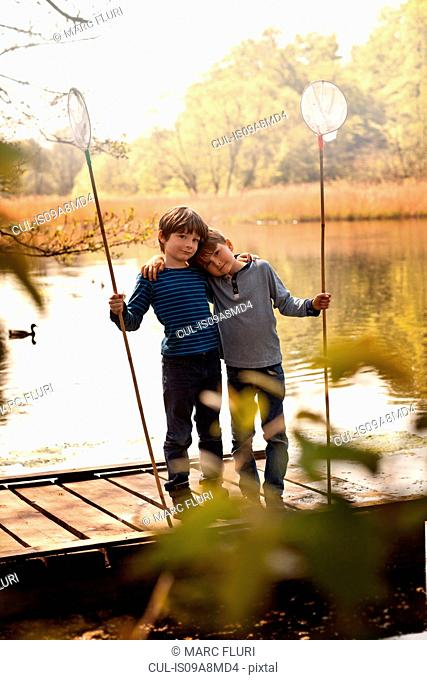 Brothers standing together on pier holding fishing nets, portrait