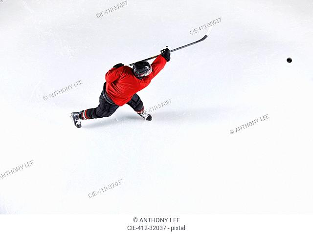 Hockey player in red uniform shooting puck on ice