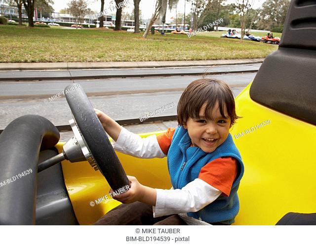 Mixed race boy driving go-cart