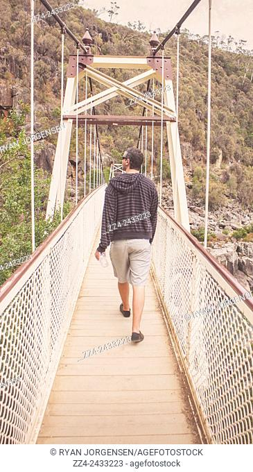 Old style photograph on the rear view of a casual man walking across the Alexandra Suspension Bridge while on holidays to Cataract Gorge in Launceston, Tasmania