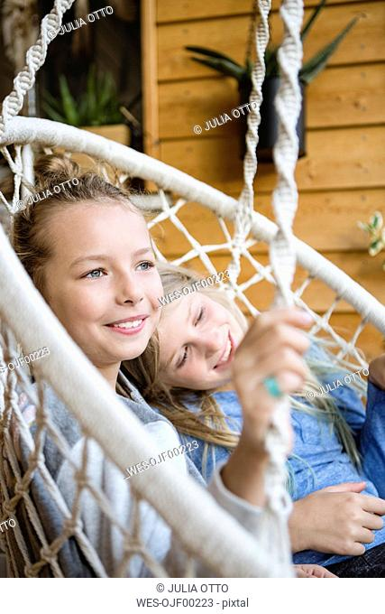 Two happy girls relaxing together in a hanging chair