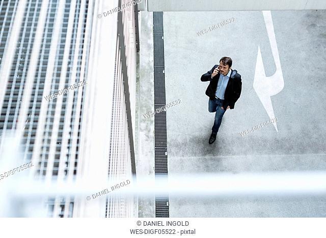Businessman walking in parking garage, using mobile phone