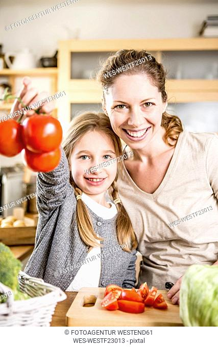Mother and daughter preparing salad in kitchen
