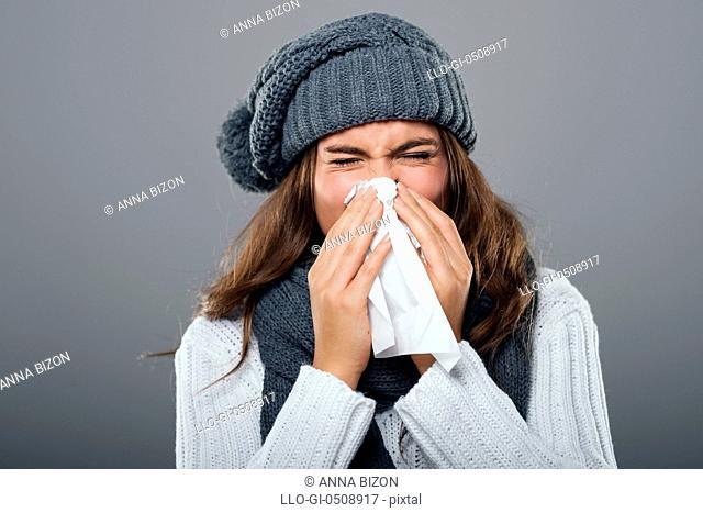 Woman in winter clothes sneezing Debica, Poland