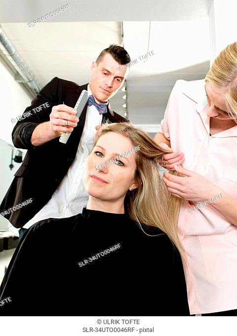Hairdressers examining woman?s hair