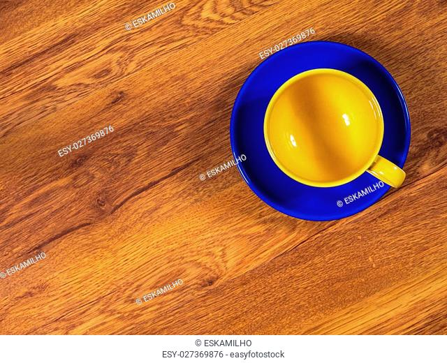 Top view on the cup with saucer, standing on the wooden table