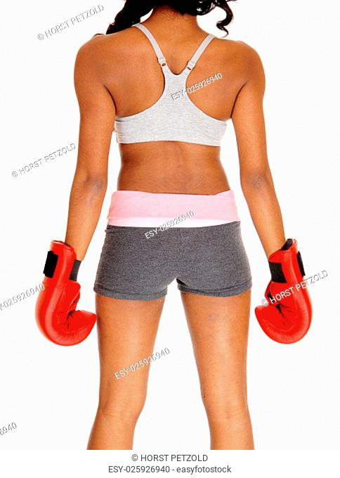 A young pretty African American woman in sportswear, wearing red.boxing gloves, standing from the back, isolated for white background.