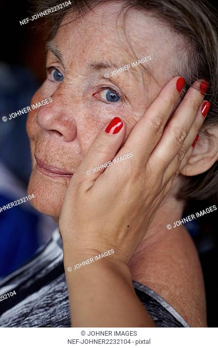 Womans hand touching senior woman face