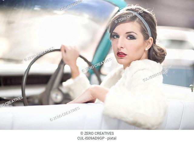 Woman at wheels of vintage car turning around
