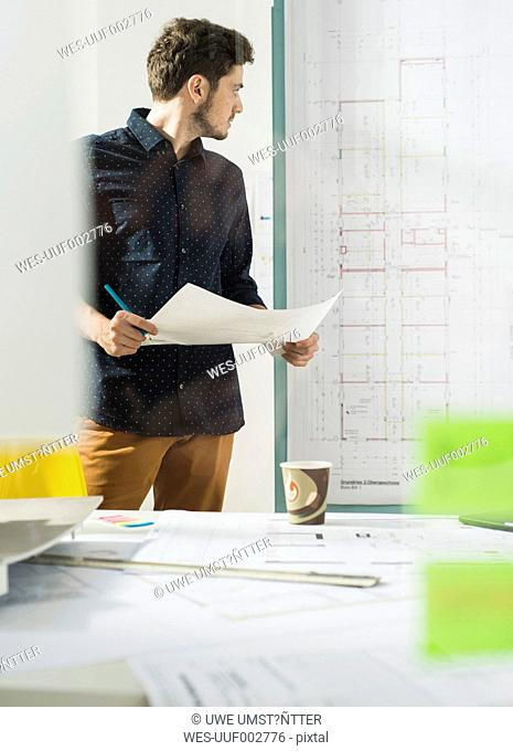 Young architect in office looking at construction plan