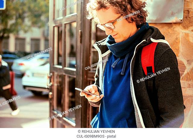 Man reading text message by door