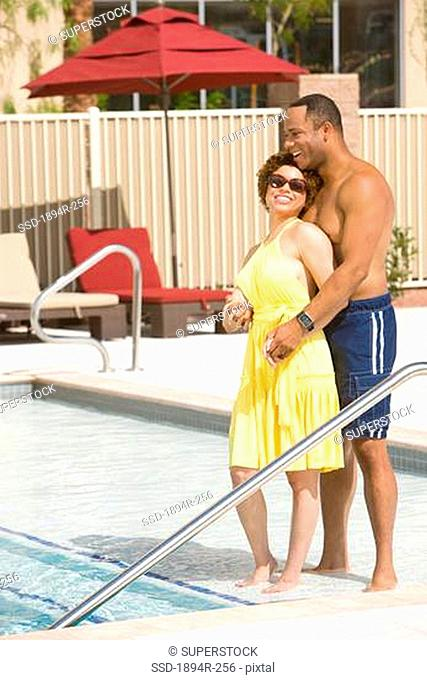 Young couple romancing at the poolside