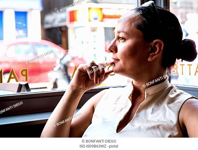 Businesswoman with hand on chin in coffee bar
