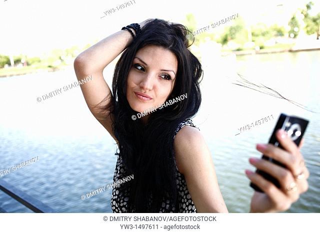 25 year old pretty woman outdoors taking photo of herself