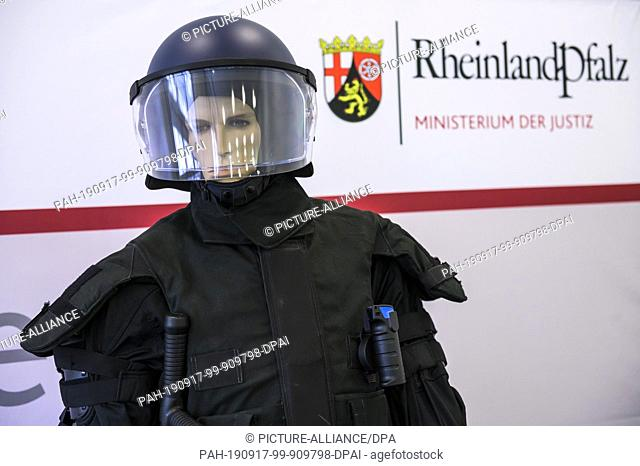 16 September 2019, Rhineland-Palatinate, Mainz: At a press conference at the Ministry of Justice, an overall, a helmet, pepper spray (r) and the new baton are...