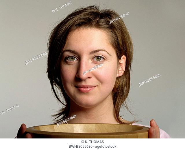 Young Woman / twen, holding a wooden bowl in front of her body