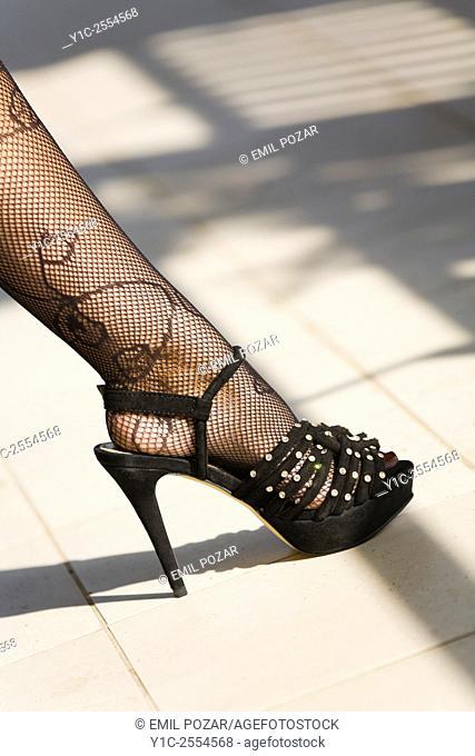Stock Photo - Leg only female high-heeled shoe and fishnet stockings