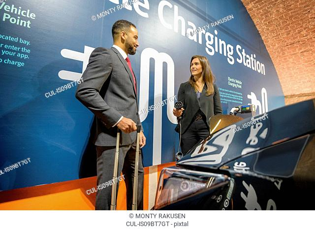 Businessman and businesswoman at electric vehicle charging station, Manchester, UK