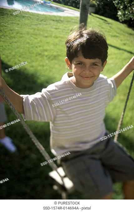 Portrait of a boy swinging on a rope swing