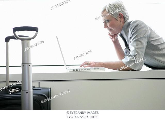 Mature woman using laptop in airport