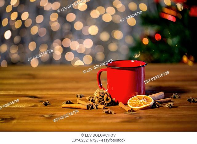 christmas, holidays, cooking and spice concept - close up of tea cup with cinnamon, anise and dried orange on wooden table over lights