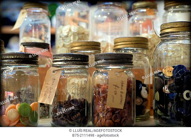 A lot of buttons in glass jars with a description and a price in a warehouse, London, England, UK. Europe