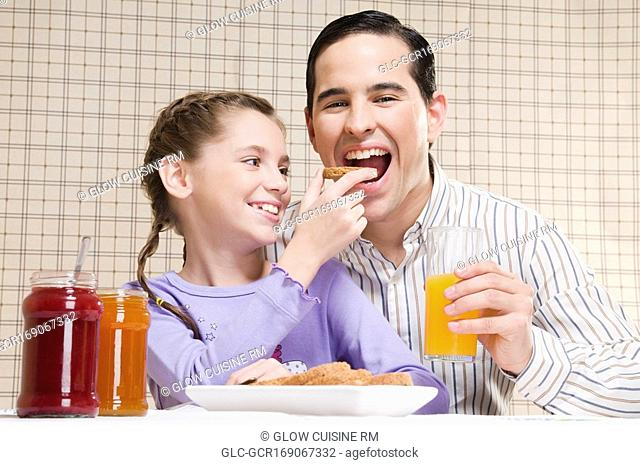 Close-up of a girl feeding toast to her father