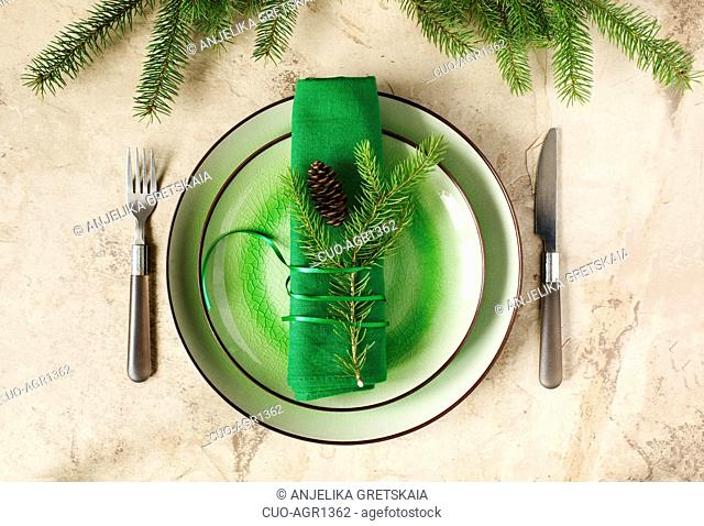 Two green empty round plates with napkin, fork and knife and Christmas decoration - fir tree brunch and cones, top view. Christmas menu background