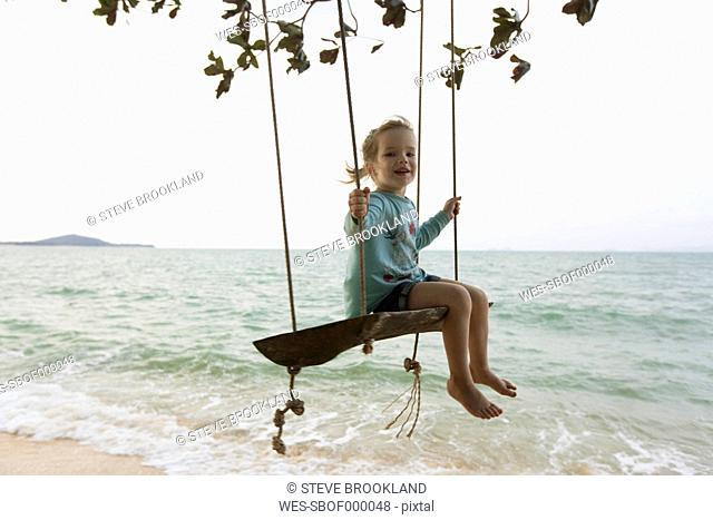 Young girl on beach, sitting on swing in Thailand