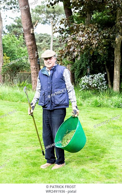 Senior man holding bucket with weeds