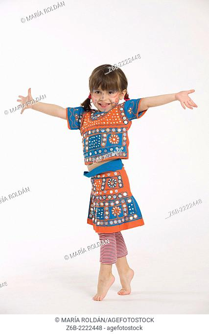 3 years old little girl dressed in a coustume from India standing on tiptoe