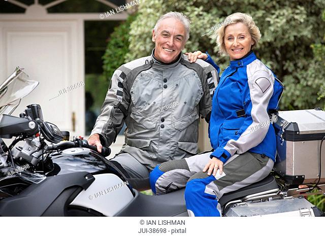 Portrait of happy senior couple on motorcycle in driveway