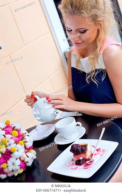 a beautiful young blond girl in summer dress at the table in pavement cafe is pouring tea from the teapot into the cup