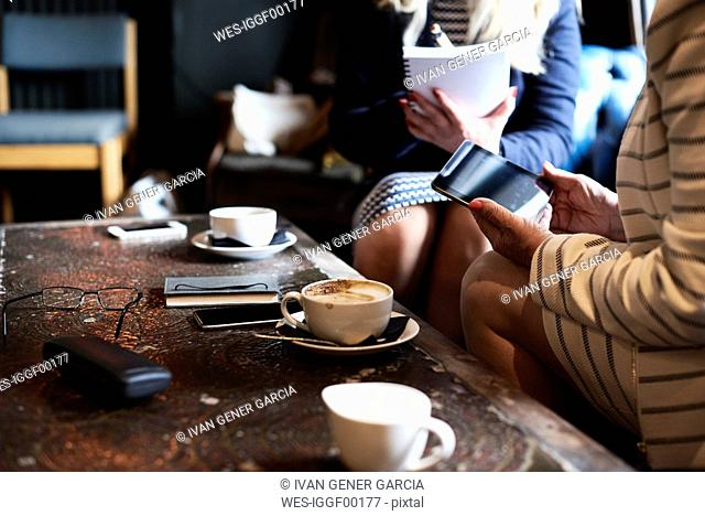 Two businesswomen with tablet and notebook having a meeting at a coffee shop