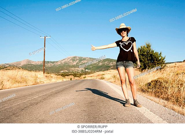 Woman hitch hiking on rural road