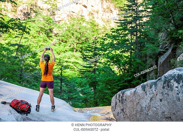 Female hiker photographing valley with smartphone on way to Daecheongbong peak, Seoraksan National Park in South Korea