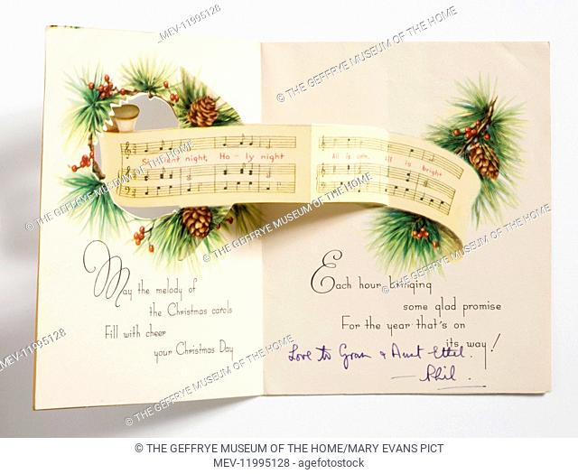 Christmas card printed with a design of a group of carol singers below a fir branch motif with pine cones and two blue tits